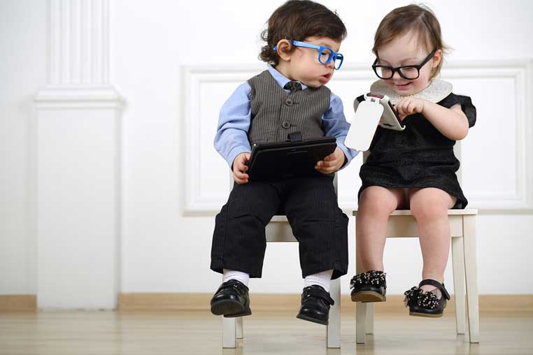Two little kids reading about need blind admissons