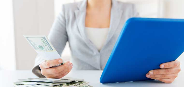 woman holding tablet and money representing financial aid tips