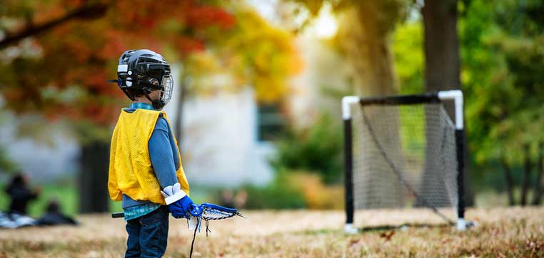 little kid playing lacrosse representing athletic scholarship reality check