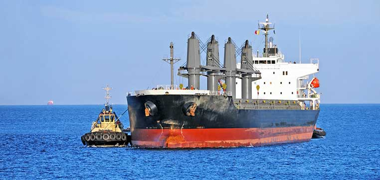 tug boat pushing larger ship representing why you should consider going to a smaller college